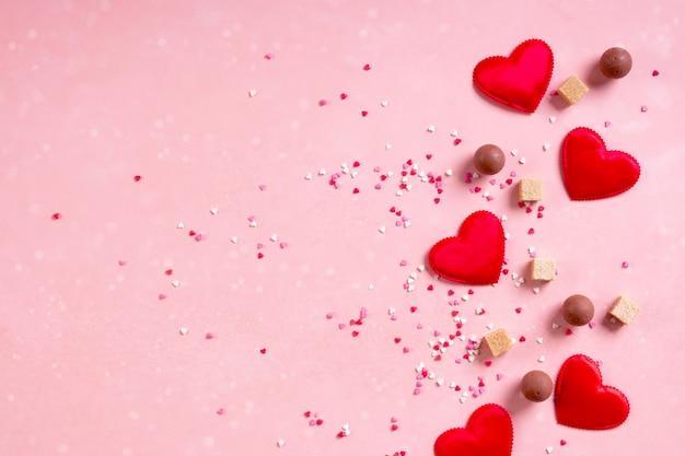 Coeurs en tissu rouge, morceaux de sucre, confettis, bonbons chocolat bonbons sur fond rose. valentin le 14 février aime le concept minimal. mise à plat, espace copie, espace pour le texte, bannière