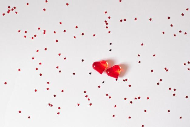 Coeurs en verre rouge sur blanc avec des confettis.