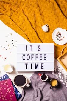 Coffee time est écrit sur une lampe décorative parmi les nombreuses tasses de café