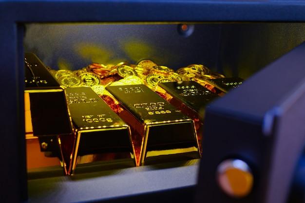 Coffre-fort en acier plein de pile de pièces et de lingot d'or sur la table en bois