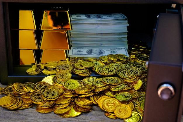 Coffre-fort en acier plein de pile de pièces de monnaie et de lingots d'or et de billets de 100 usd sur la table en bois