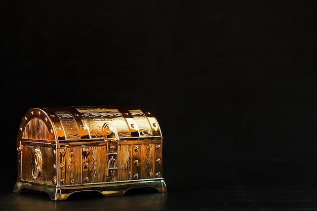 Un coffre en or avec des bijoux sur fond noir