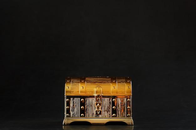 Un coffre en or avec des bijoux sur une surface noire avec espace copie