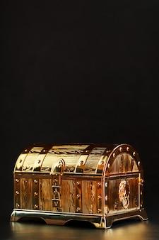 Un coffre en or avec des bijoux sur une table noire