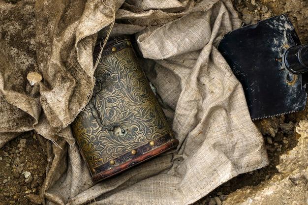 Coffre vintage déployé à partir d'un paquet de tissus excavé du sol et d'un outil de creusement de tranchées dans la fosse