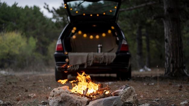 Coffre de la voiture ouvert à côté d'un feu de joie