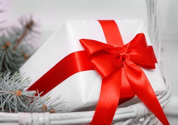 Coffret blanc avec arc rouge et branches d'épinette dans un panier en osier, gros plan