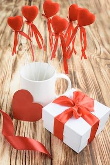 Coffret blanc avec noeud riibon rouge, tasse blanche avec coeurs rouges sur bâton, carte coeur et fleurs roses de ruban de satin sur fond en bois.