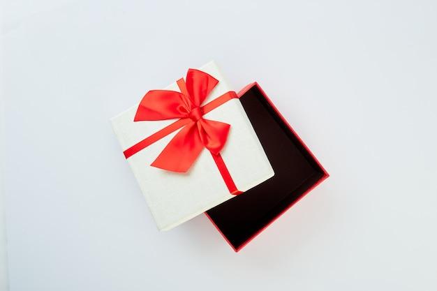 Coffret blanc avec noeud de ruban rouge sur blanc