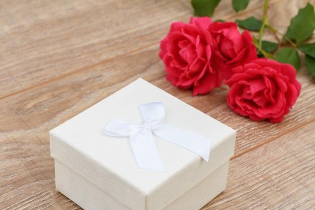 Coffret blanc avec des roses rouges sur le fond en bois. concept de donner un cadeau en vacances. vue de dessus.