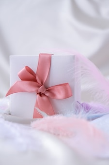 Coffret blanc avec ruban rose sur fond de texture de soie blanche. plume d'oiseau colorée. notion de vacances. cadeau pour la saint-valentin anniversaire des mères fête des femmes