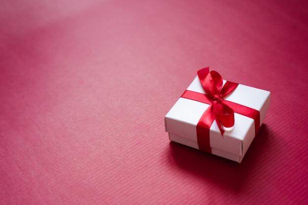Coffret blanc avec ruban de satin et noeud sur fond de papier rouge cramoisi avec copie espace