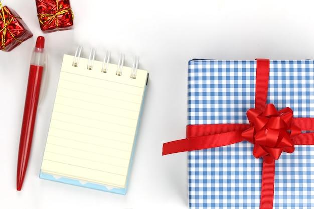Coffret bleu de noël et du nouvel an et cahier vierge sur fond blanc.