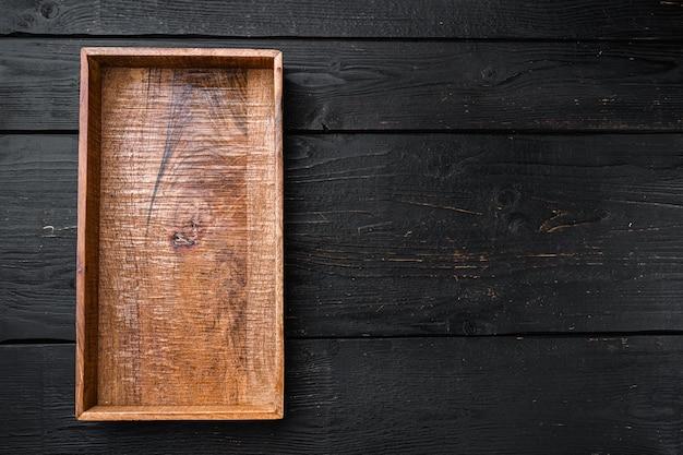 Coffret en bois sombre vide avec espace de copie pour le texte ou la nourriture, vue de dessus à plat, sur fond de table en bois noir