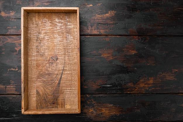 Coffret en bois sombre vide avec espace de copie pour le texte ou la nourriture, vue de dessus à plat, sur fond de table en bois sombre ancien