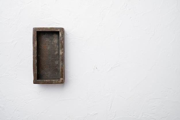 Coffret en bois sombre vide avec espace de copie pour le texte ou la nourriture, vue de dessus à plat, sur fond de table en pierre blanche