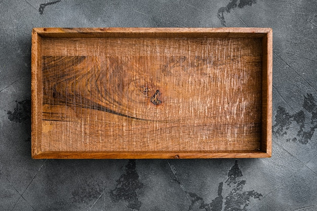 Coffret en bois sombre vide avec espace de copie pour le texte ou la nourriture, vue de dessus à plat, sur fond de table en pierre grise