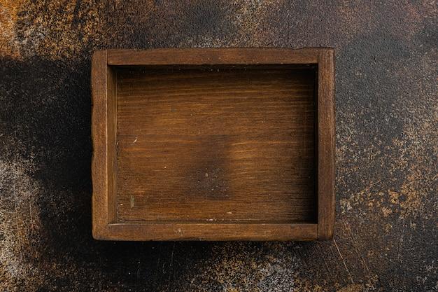 Coffret en bois sombre vide avec espace de copie pour le texte ou la nourriture, vue de dessus à plat, sur un vieux fond de table rustique sombre