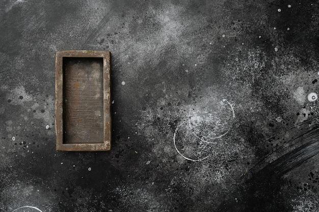 Coffret en bois vide avec espace de copie pour le texte ou la nourriture, vue de dessus à plat, sur fond de table en pierre noire noire