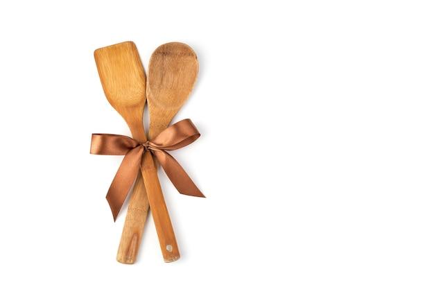 Coffret cadeau d'accessoires de cuisine à égalité avec un ruban de satin sur fond blanc.