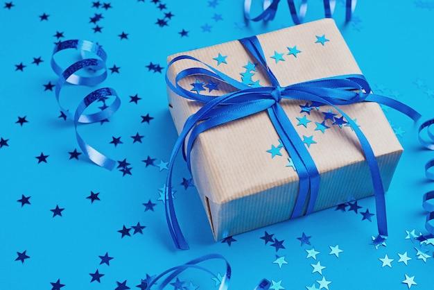 Coffret cadeau avec un arc et des confettis, gros plan