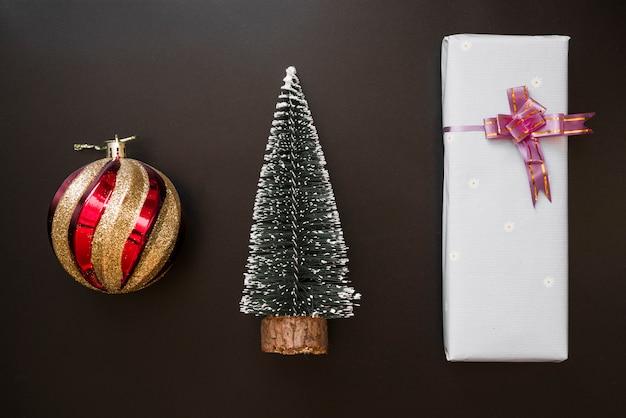 Coffret cadeau avec un arc près d'une boule décorative et d'un sapin