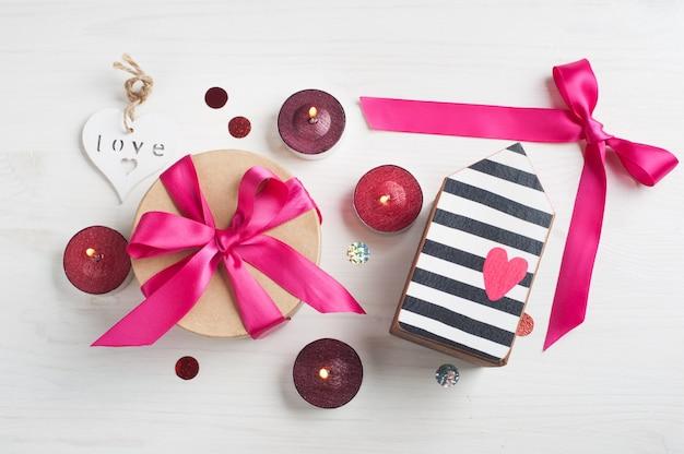 Coffret cadeau avec un arc rose et des bougies allumées