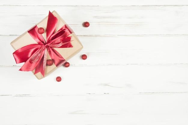 Coffret cadeau avec un arc rouge et des ballons rouges sur un fond en bois blanc