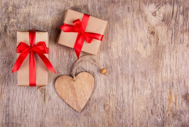 Coffret cadeau avec un arc rouge et un cœur en bois sur une vieille table en bois.