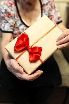 Coffret cadeau avec arc rouge dans les mains de grand-mère macro