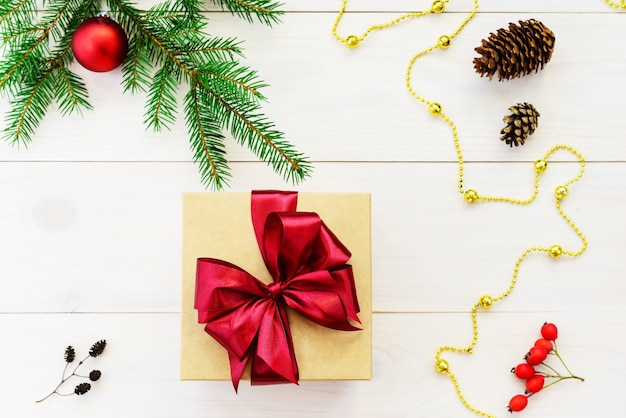 Coffret cadeau avec un arc rouge sur une table en bois clair. cadeau pour noël et nouvel an.