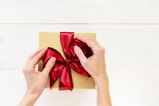 Coffret cadeau avec un arc rouge sur une table en bois clair.