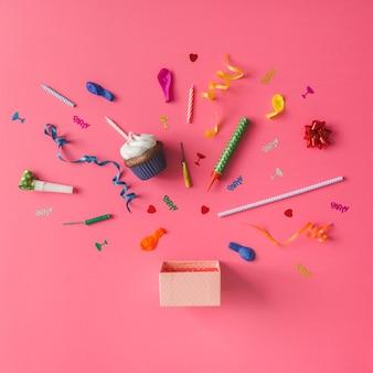 Coffret cadeau avec des articles de fête colorés sur un mur rose. mise à plat.