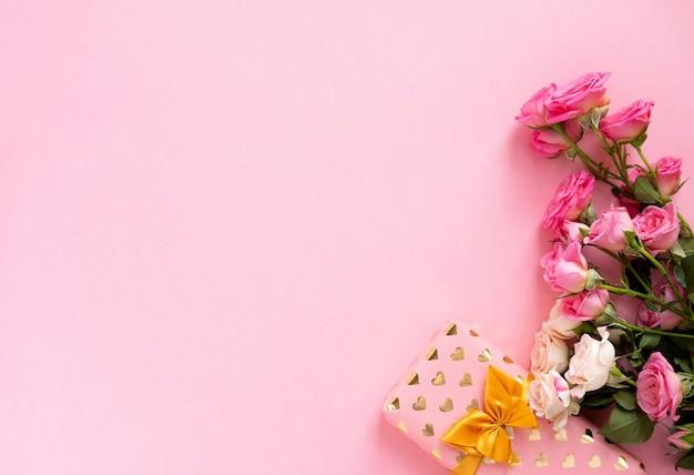 Coffret cadeau avec un beau ruban doré et des roses, de la saint-valentin, de la fête des mères et des voeux d'anniversaire.