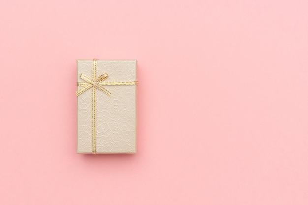 Coffret cadeau beige avec archet sur fond pastel rose dans un style minimal.