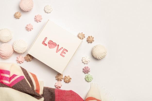 Coffret cadeau, belle écharpe, meringues et bonbons sur fond clair. composition saint-valentin. bannière. mise à plat, vue de dessus.