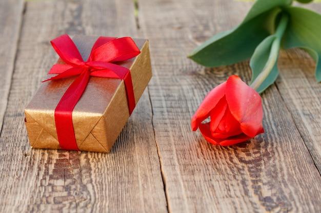 Coffret cadeau avec une belle tulipe sur le fond en bois. concept de donner un cadeau en vacances. vue de dessus.