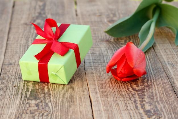 Coffret cadeau avec belle tulipe rouge sur le fond en bois. concept de donner un cadeau en vacances. vue de dessus.