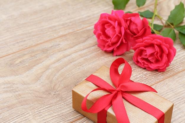 Coffret cadeau avec de belles roses rouges en arrière-plan. concept de donner un cadeau en vacances. vue de dessus.