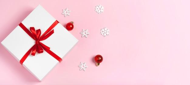 Coffret cadeau blanc de luxe avec ruban rouge et flocons de neige sur fond rose avec espace de copie isolé à plat. composition minimaliste. concept de vacances d'hiver noël, nouvel an, anniversaire, réductions.
