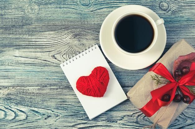 Coffret cadeau, bloc-notes avec un cœur et une tasse de café sur un fond en bois gris-bleu.