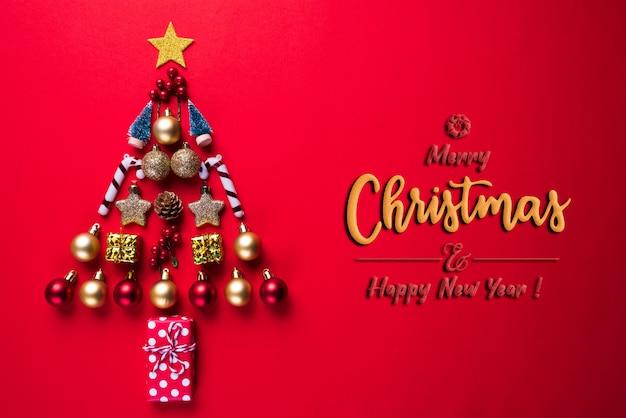 Coffret cadeau avec boule rouge et cloche en forme d'arbre de noël sur fond rouge.