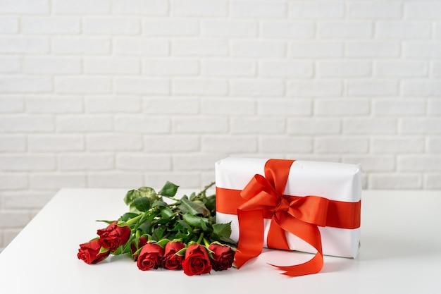 Coffret cadeau avec bouquet de roses sur une table blanche pour la saint valentin