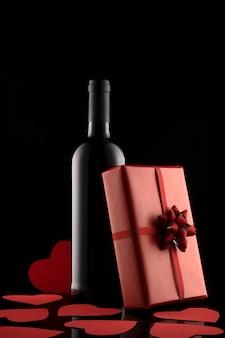Coffret cadeau, bouteille de vin et coeurs rouges carte de voeux romantique et invitation. composition de la saint-valentin.