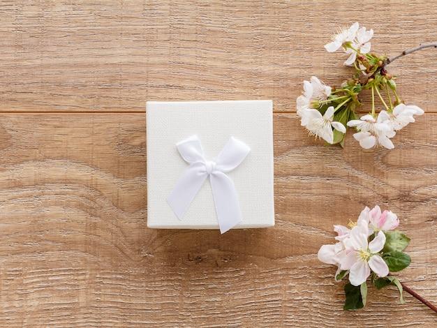 Coffret cadeau avec des branches de cerisier en fleurs et de pommiers sur le fond en bois. vue de dessus. concept de donner un cadeau en vacances.