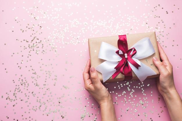 Coffret cadeau ou cadeau avec un grand arc dans les mains d'une femme sur une table rose. composition plate pour noël, anniversaire, fête des mères ou mariage.