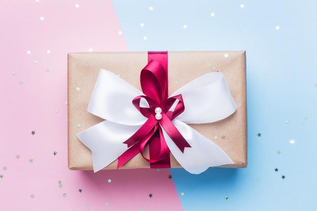 Coffret cadeau ou cadeau avec un grand noeud sur une vue de dessus de table bleu rose. composition plate pour noël, anniversaire, fête des mères ou mariage.