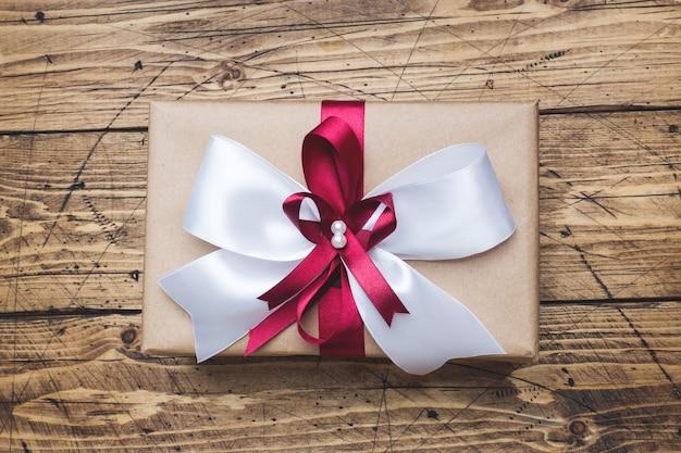 Coffret cadeau ou cadeau avec un grand noeud sur une vue de dessus de table en bois. composition plate pour noël, anniversaire, fête des mères ou mariage.