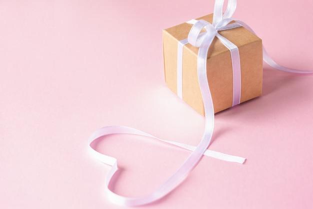 Coffret cadeau ou cadeau avec ruban blanc sur fond rose.