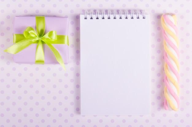 Coffret cadeau et cahier ouvert avec une page vierge.